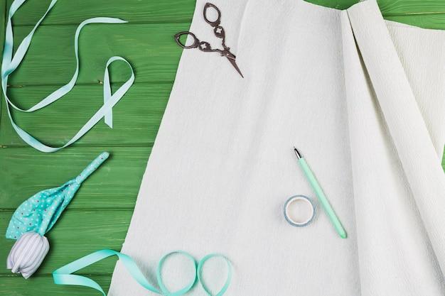Materiale del mestiere di mano con fiori finti su sfondo verde