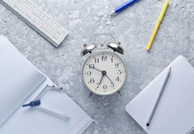 Materiale didattico. sveglia, blocco note, righello, penna, bussole. vista dall'alto, stile piatto