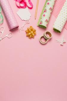 Materiale e accessori per il confezionamento di regali disposti su una superficie rosa