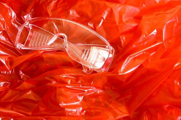 Materiale protettivo sintetico rosso con occhiali di sicurezza per la sicurezza.