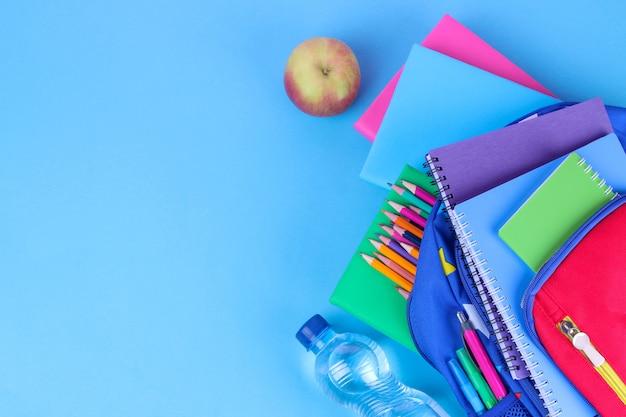 Materiale scolastico che cade da uno zaino scuola su uno sfondo blu brillante.
