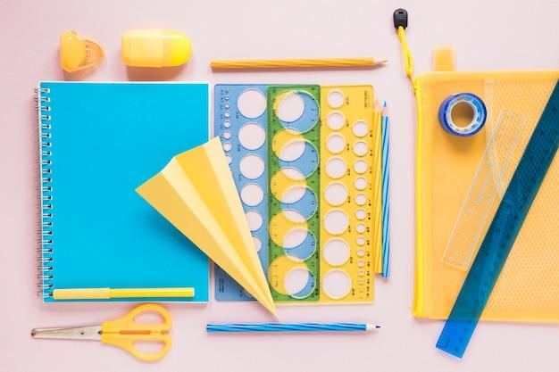 Materiale scolastico colorato laico piatto