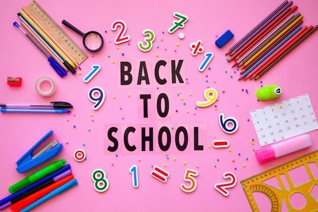 Materiale scolastico con lettere di ritorno a scuola. torna al concetto di scuola. cancelleria e lettere di scarabeo sul tavolo.