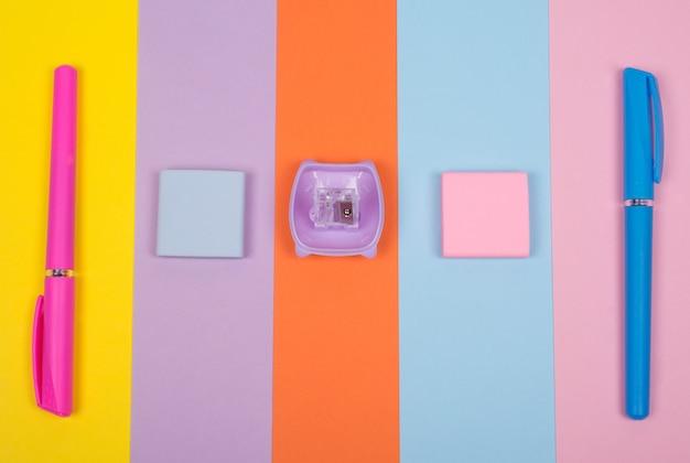 Materiale scolastico di fila su uno sfondo di carta multicolore