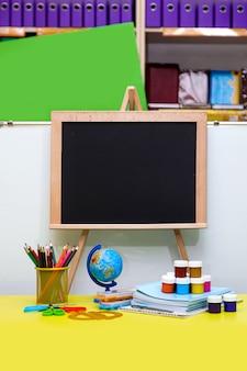 Materiale scolastico e cancelleria, scrivania, globo, matite, penne, quaderni, lavagna nera sul tavolo giallo.