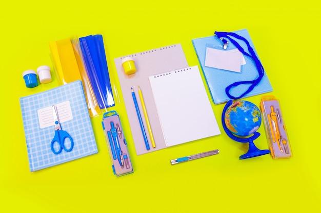 Materiale scolastico e cancelleria, scrivania, globo, matite, penne, quaderni sul tavolo giallo.