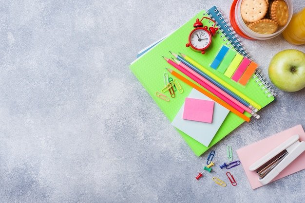 Materiale scolastico e cracker per colazione, succo d'arancia e mela fresca
