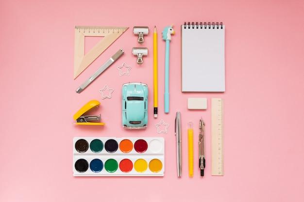 Materiale scolastico giallo su sfondo rosa pastello