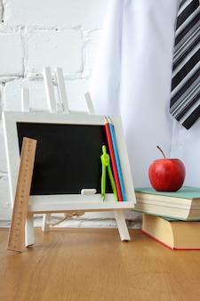 Materiale scolastico, lavagna in miniatura, una pila di libri e una mela sul tavolo