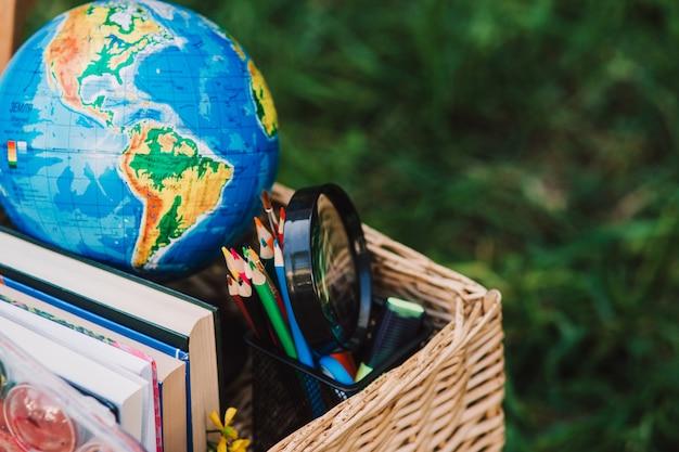 Materiale scolastico, libri e globo nel cestino