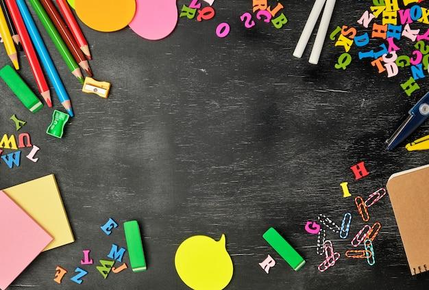 Materiale scolastico sfondo con matite colorate in legno, taccuino, adesivi di carta, graffette