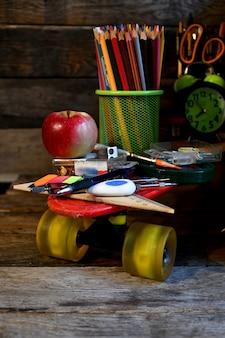 Materiale scolastico situato su uno skateboard.