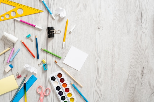 Materiale scolastico su fondo in legno. torna al concetto di scuola.