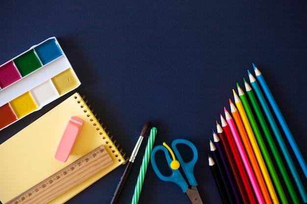 Materiale scolastico su sfondo blu scuro.