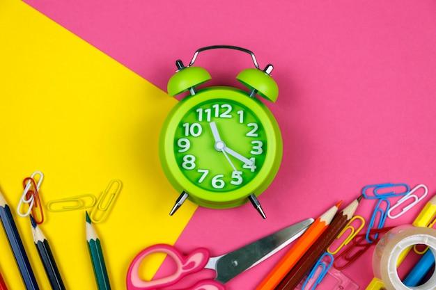 Materiale scolastico su sfondo colorato.