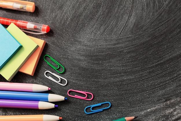 Materiale scolastico su sfondo di lavagna