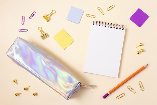 Materiale scolastico su uno sfondo beige chiaro.