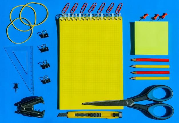 Materiale scolastico vista dall'alto, disposto su carta blu, illuminazione solare