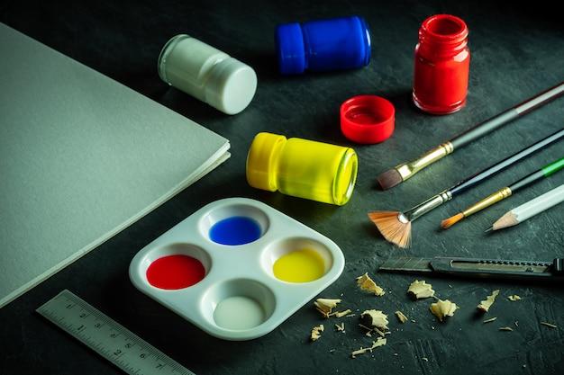 Materiali artistici e bottiglia di colore per poster sul pavimento di cemento nero