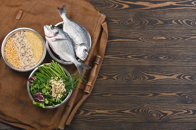 Materie prime naturali per ingredienti sani per animali domestici in singole ciotole su legno marrone.