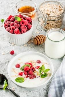 Materie prime per una sana colazione estiva, cereali (avena), lampone fresco, foglie di menta, yogurt, miele, su cemento leggero, copyspace