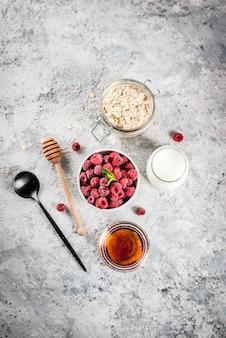 Materie prime per una sana colazione estiva, cereali (avena), lampone fresco, foglie di menta, yogurt, miele, su cemento leggero, vista dall'alto, copyspace
