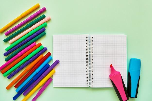 Materie scolastiche su sfondo verde. pennarelli e blocco note su sfondo verde. torna al concetto di scuola. disteso, copia spazio