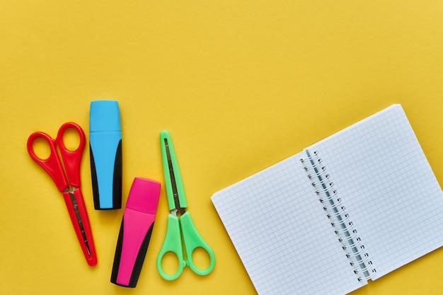 Materie scolastiche su uno sfondo giallo. blocco note, forbici colorate e pennarelli. torna al concetto di scuola. disteso, copia spazio