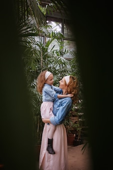 Maternità ed emozioni di felicità e gioia di madre e figlia. una giovane madre tiene la sua piccola figlia felice tra le braccia, sollevandola e la guarda sullo sfondo del verde