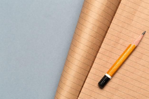 Matita corta indossata con blocco note sulla scrivania grigia