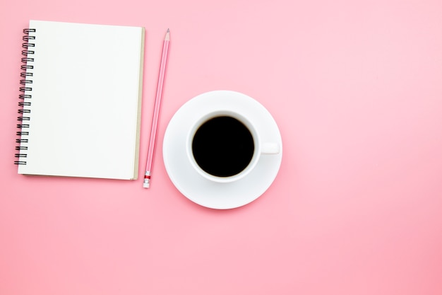 Matita del caffè nero del taccuino su stile pastello del fondo rosa