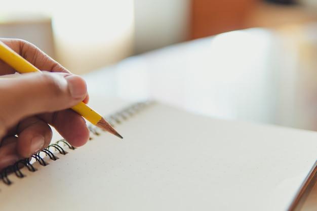 Matita di giallo della tenuta della mano del primo piano con il taccuino facendo uso di come concetto di istruzione e di affari