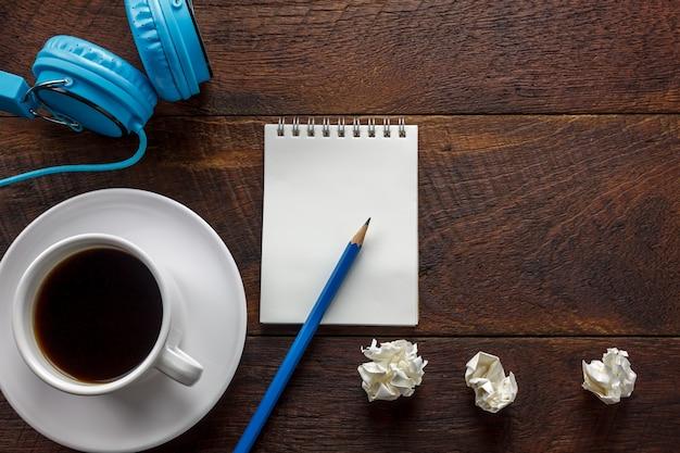 Matita di vista dall'alto, carta di nota, carta nera di caffè sgualcita, cuffie sulla scrivania con spazio di copia.