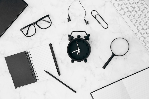 Matita; diario; occhiali; auricolare; graffetta per fogli; lenti d'ingrandimento; sveglia con tastiera e diario sullo scrittorio bianco