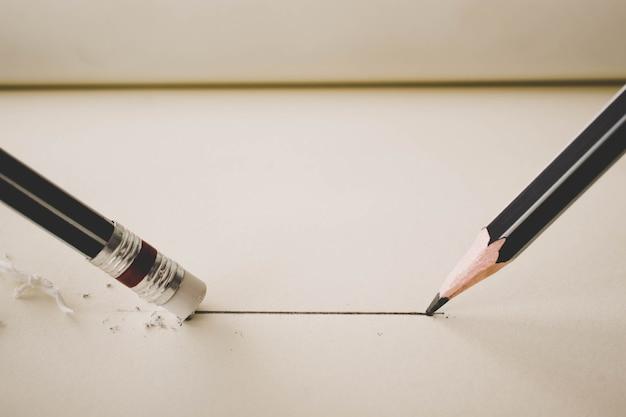 Matita disegna una linea retta su carta e gomma da matita rimuovendo la striscia. concetto di business breaking.
