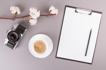 Matita e carta sulla lavagna per appunti vicino alla macchina fotografica, ramoscello della pianta e tazza