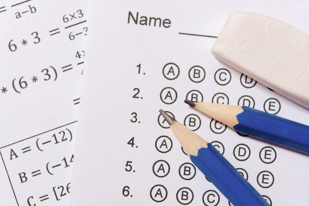 Matita e gomma su fogli di risposta o modulo di prova standardizzato con le risposte gorgogliate. foglio di risposta a scelta multipla