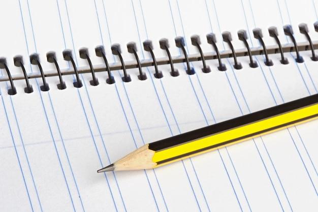 Matita e quaderno su un terreno posteriore bianco
