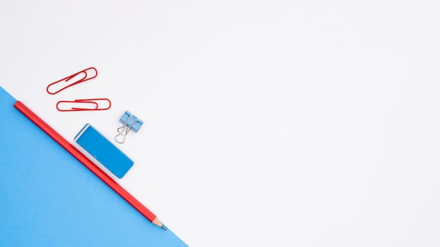Matita; gomma e graffetta con carta di carta blu su sfondo bianco