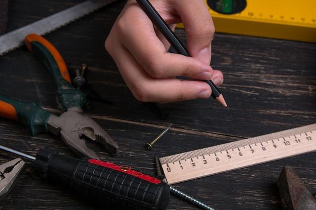 Matita nella mano di un ingegnere e costruttore. vecchi strumenti domestici della costruzione su una tavola di legno scura.