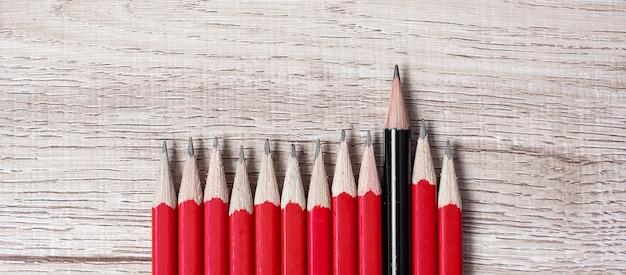 Matita nera diversa dalla folla di matite rosse. leader unico, strategia, indipendenza, pensiero diverso, business e successo