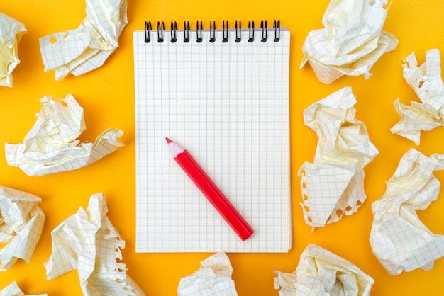 Matita rossa e taccuino su uno sfondo giallo. fogli di carta accartocciati