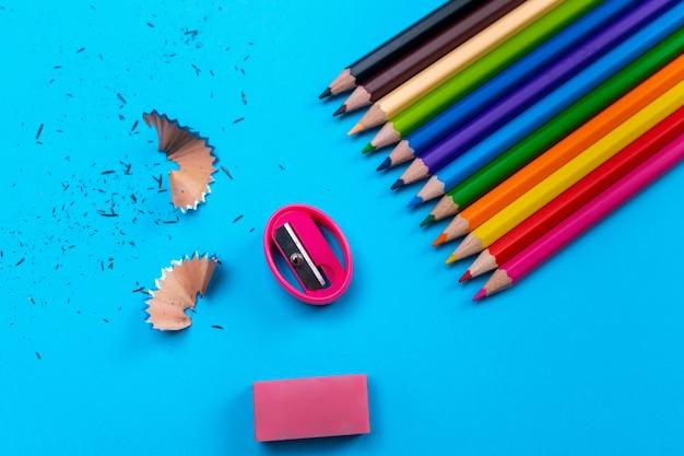 Matite colorate brillanti piegate in fila al centro di una parete blu con un rammendo e una gomma rosa e trucioli di matita.