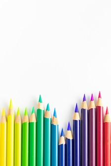 Matite colorate con sfondo bianco ordinate per tavolozze di colori