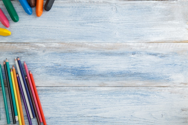 Matite colorate e pastelli su un blu e bianco sfregiato legno vintage, vista dall'alto