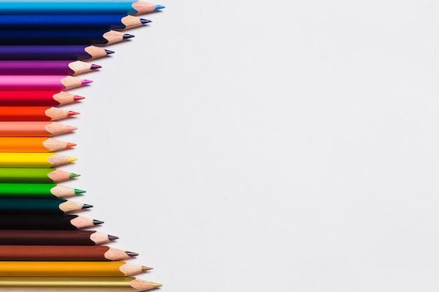 Matite colorate e un foglio di carta bianco su sfondo bianco