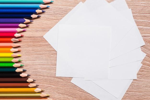 Matite colorate e un foglio di carta bianco su un fondo di legno