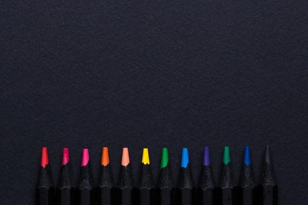 Matite colorate in fila sul nero