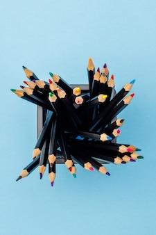 Matite colorate in una tazza nera dell'ufficio