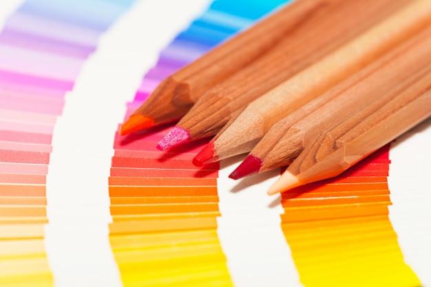 Matite colorate rosse e rosa e cartella colori di tutti i colori